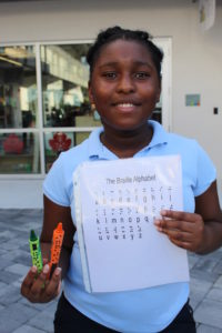Kayla with her braille crayon