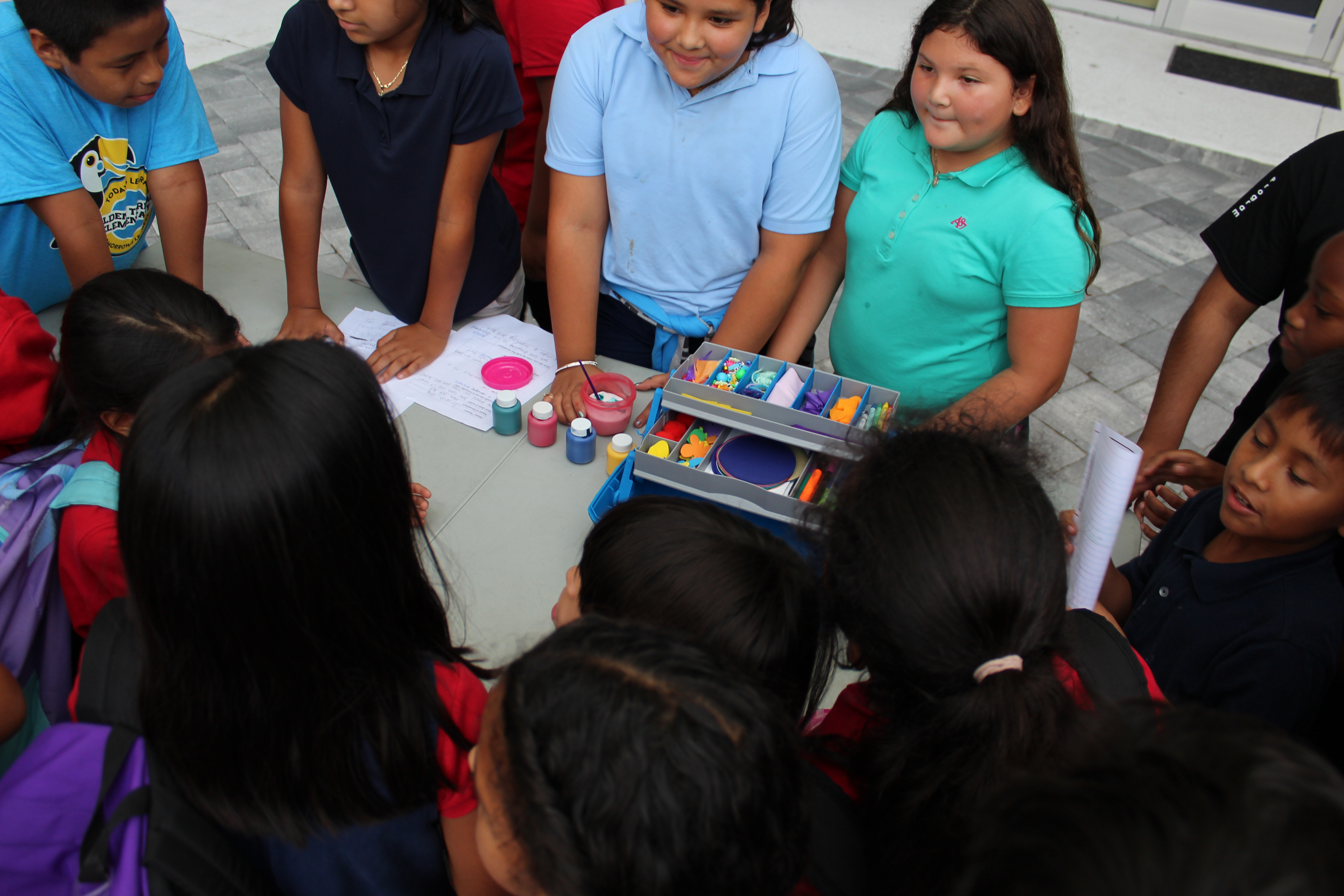 girls showing off their art kit invention